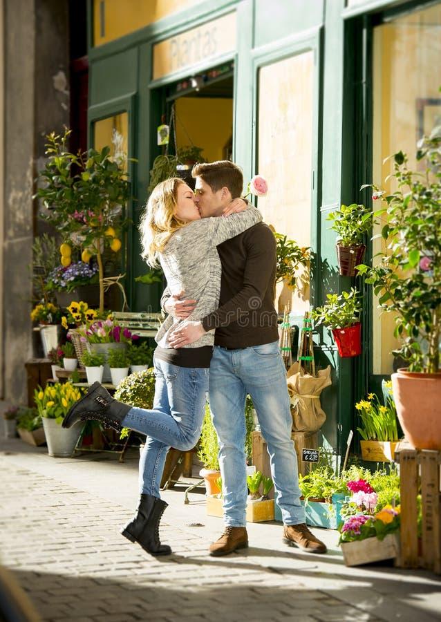 Jong mooi paar in liefde het kussen op straat het vieren Valentijnskaartendag met roze gift stock afbeelding