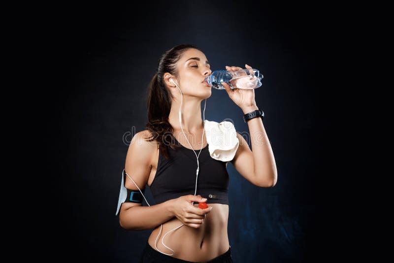 Jong mooi sportief meisjes drinkwater over donkere achtergrond stock afbeelding