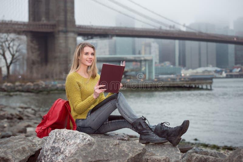 Jong mooi studentenmeisje die een boekzitting lezen dichtbij de Stadshorizon van New York royalty-vrije stock afbeelding