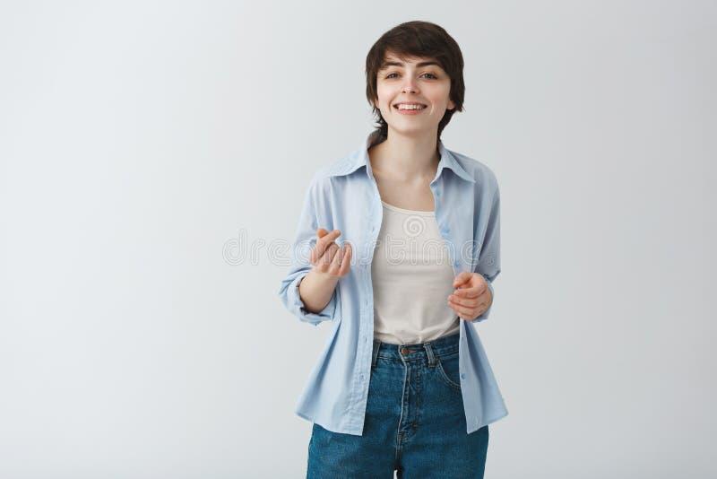 Jong mooi studentenmeisje met kort haar en grote ogen die met tanden glimlachen, en pret het stellen voor graduatie hebben dansen stock afbeeldingen