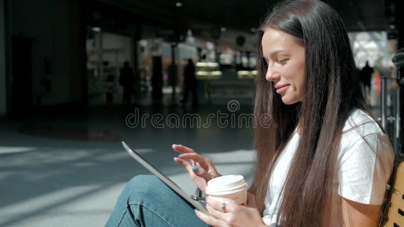 Jong mooi studentenmeisje met slimme telefoon en koffie in winkelcomplex royalty-vrije stock afbeeldingen