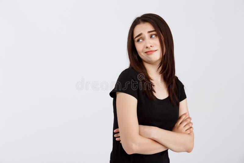 Jong mooi teleurgesteld meisje in het zwarte t-shirt stellen over witte achtergrond stock afbeelding