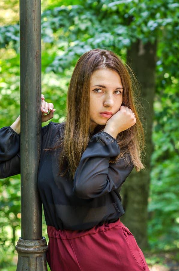 Jong mooi tienermeisje die met lang haar in Striysky-park in Lviv lopen, die dichtbij een lamp stellen om de struiken te verlicht stock foto