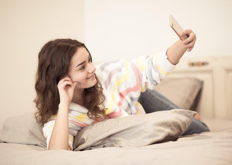Jong mooi tienermeisje die selfie op mobiele telefoon voor haar aanhangers in sociale media nemen royalty-vrije stock afbeelding