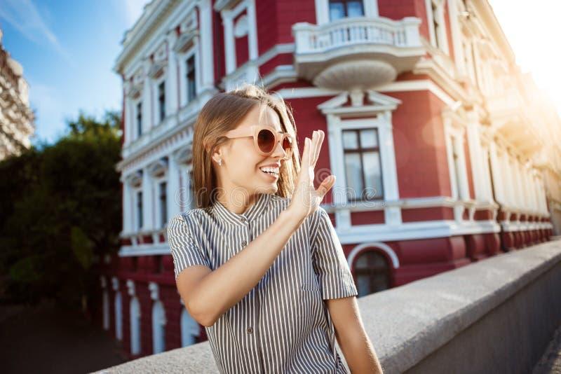 Jong mooi vrolijk meisje die in zonnebril rond stad, het glimlachen lopen Openlucht achtergrond royalty-vrije stock foto