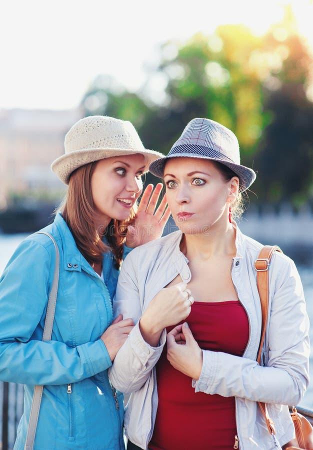 Jong mooi vrouw het vertellen geheim aan haar vriend in de stad stock foto