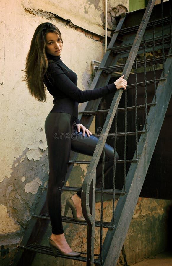 Jong mooi vrouwelijk model dat zich dichtbij muur bevindt stock fotografie