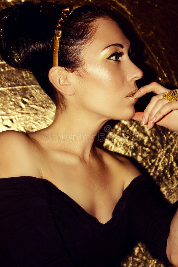 Jong mooi vrouwenbrunette met retro kapsel, hoepel Gouden samenstelling stock foto's
