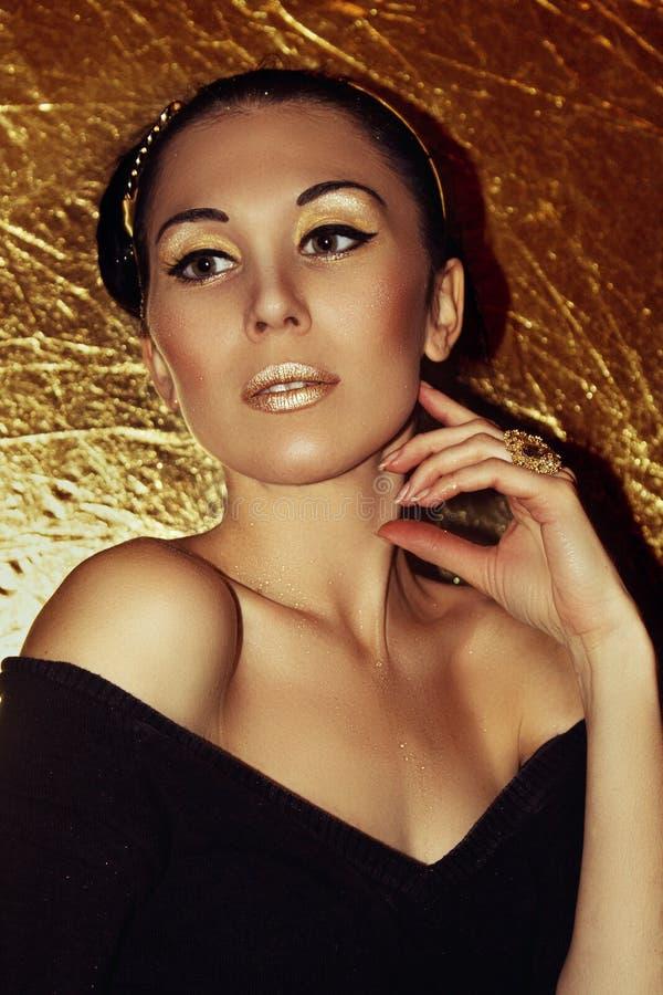 Jong mooi vrouwenbrunette met retro kapsel, hoepel Gouden samenstelling stock afbeelding