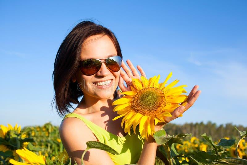 Jong mooi vrouwenmeisje op achtergrond van zonnebloemgebied stock foto