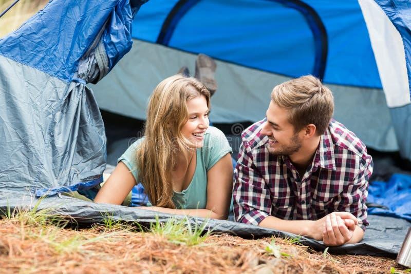 Jong mooi wandelaarpaar die in een tent liggen stock foto