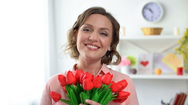 Jong mooi wijfje die bij de tulpen van de cameraholding, de lenteversheid glimlachen stock foto