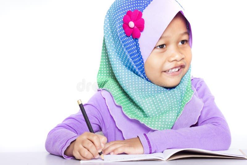 Jong moslimmeisje die een boek op het bureau schrijven stock fotografie