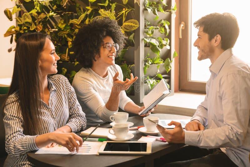 Jong multi-etnisch commercieel team die idee?n in koffie delen stock afbeelding