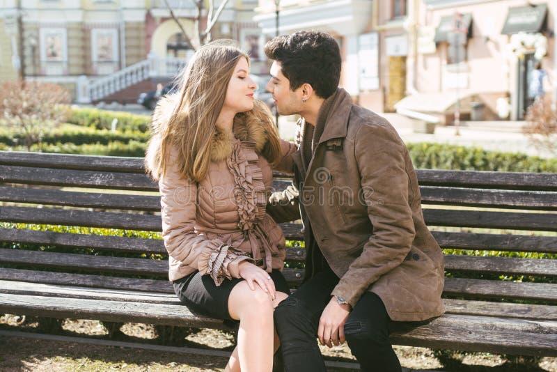Jong multiraciaal paar, mannelijke en vrouwelijke heteroseksuele studenten in liefde Een datum in een stadspark op een houten ban royalty-vrije stock afbeelding