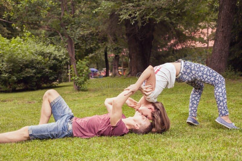 Jong ongebruikelijk kussend paar in openlucht bij park, in extreme positie royalty-vrije stock foto's