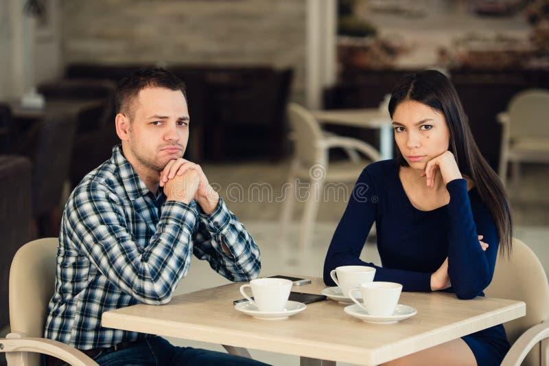 Jong ongelukkig echtpaar die ernstige ruzie hebben bij koffie stock afbeeldingen