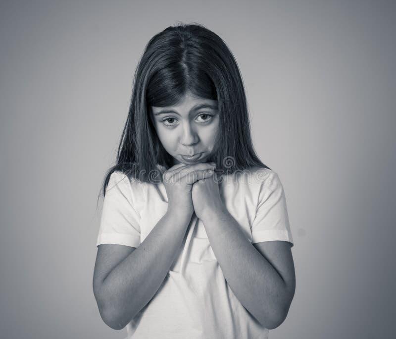 Jong ongelukkig meisje die leuke droevige gelaatsuitdrukking maken stock afbeelding
