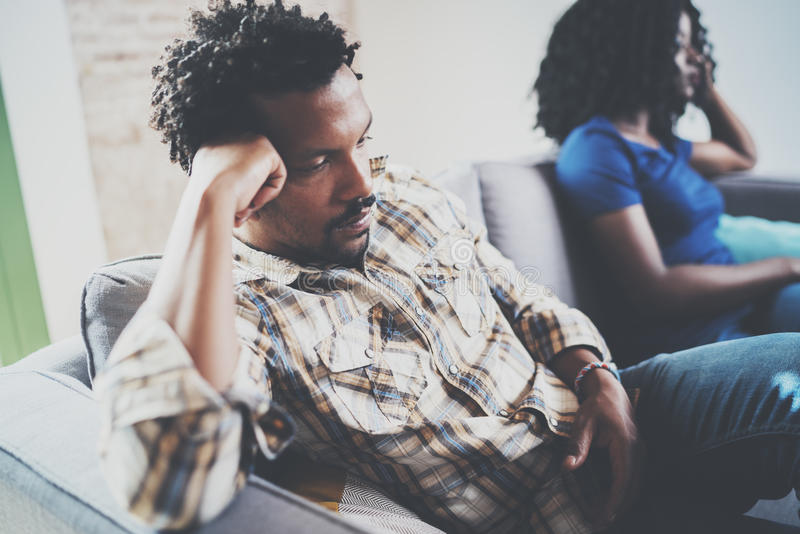 Jong ontstemd zwart paar Verstoorde mens die door partner thuis in de woonkamer worden genegeerd Het Amerikaanse Afrikaanse mense royalty-vrije stock afbeeldingen