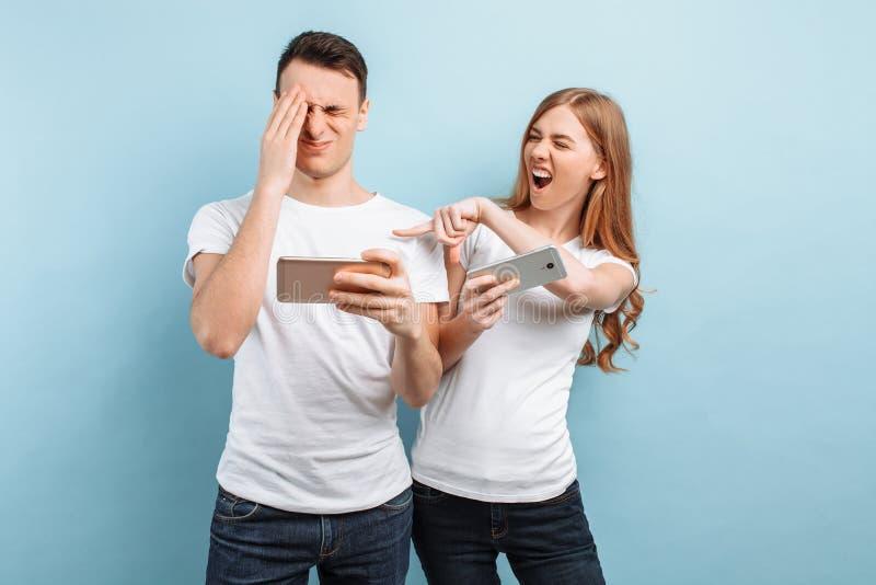 Jong opgewekt paar die, speelspelen op mobiele telefoons, op een blauwe achtergrond bevinden zich royalty-vrije stock afbeelding