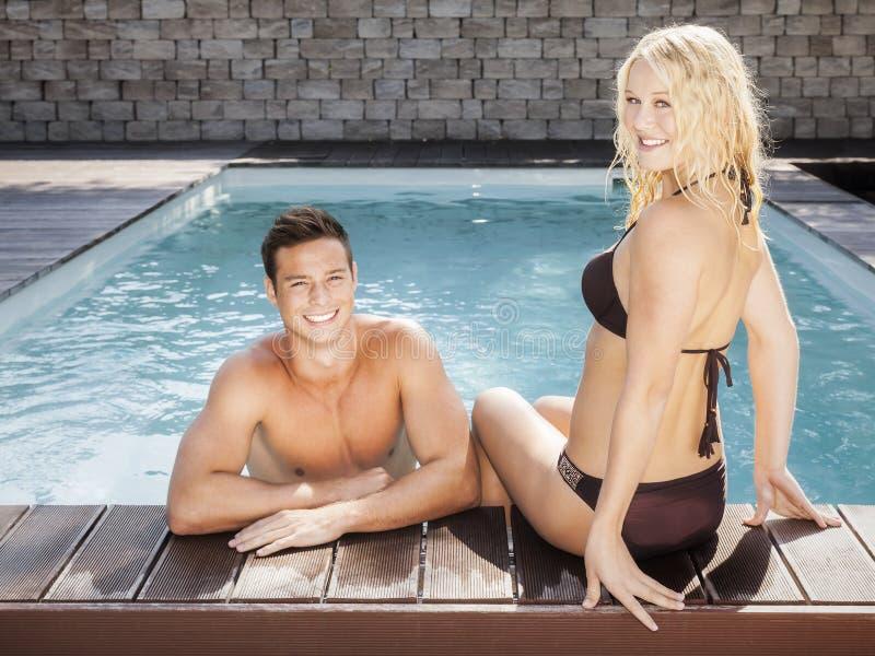 Jong paar bij de pool stock afbeeldingen