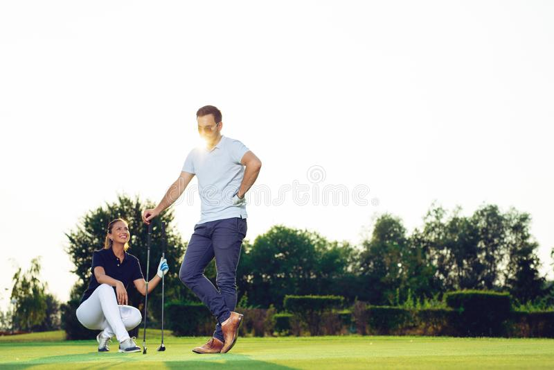 Jong paar bij golfhof stock afbeeldingen