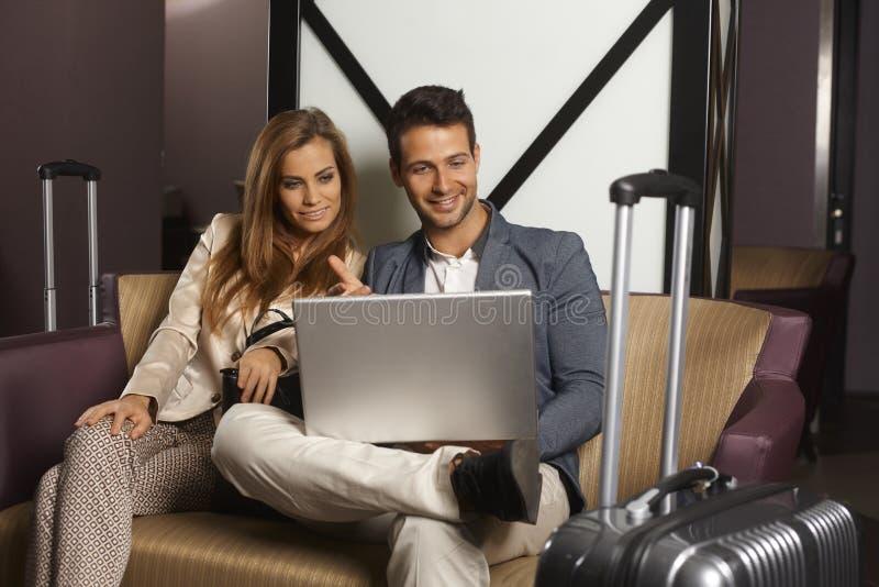 Jong paar bij hotelhal met laptop royalty-vrije stock fotografie