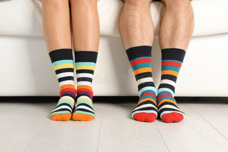 Jong paar in binnen de aanpassing van sokken op laag stock afbeeldingen