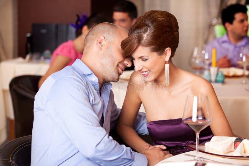 Jong paar dat bij restaurantlijst flirt stock fotografie