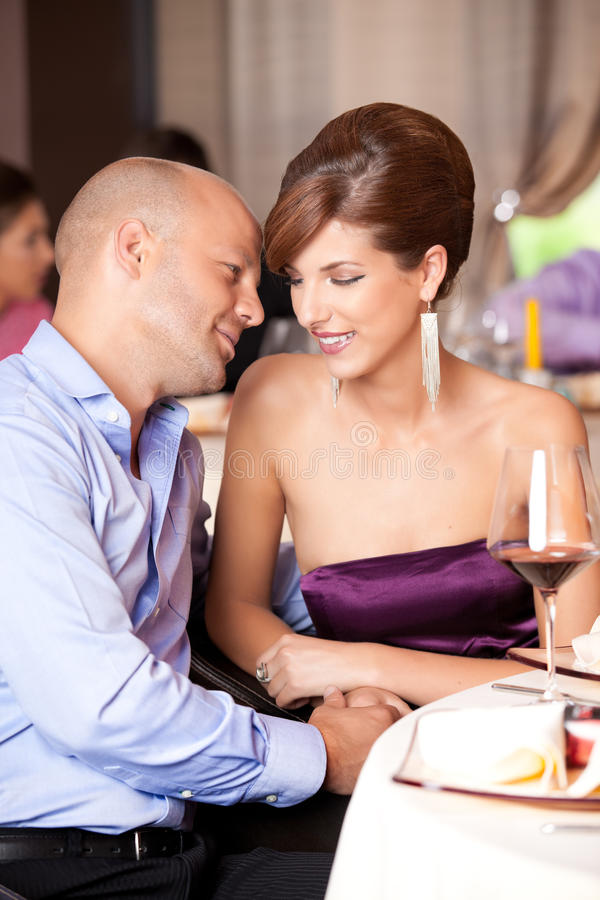 Jong paar dat bij restaurantlijst flirt royalty-vrije stock afbeelding