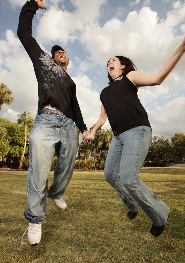 Jong paar dat in de lucht springt stock afbeelding