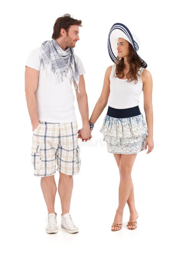 Jong paar dat in de zomeruitrusting hand in hand loopt royalty-vrije stock afbeelding