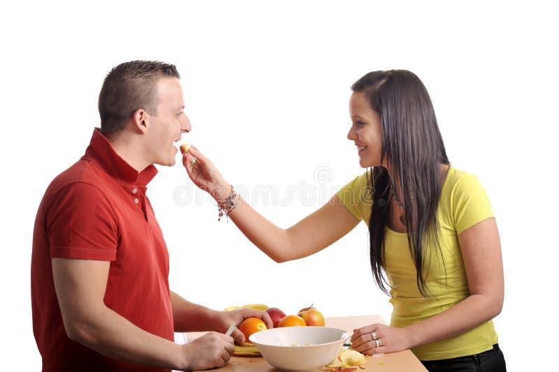 Jong paar dat een fruitsalade voorbereidt stock fotografie