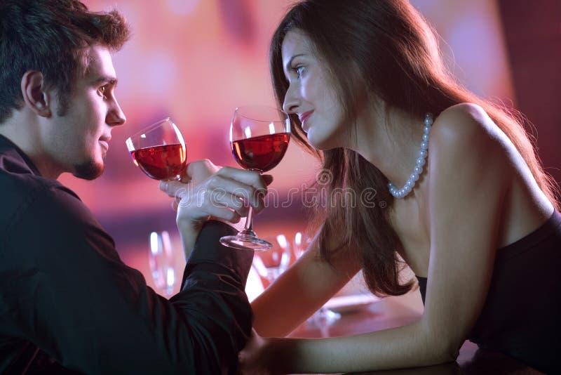 Jong paar dat een glas rode wijn in restaurant deelt, celebrat royalty-vrije stock afbeelding