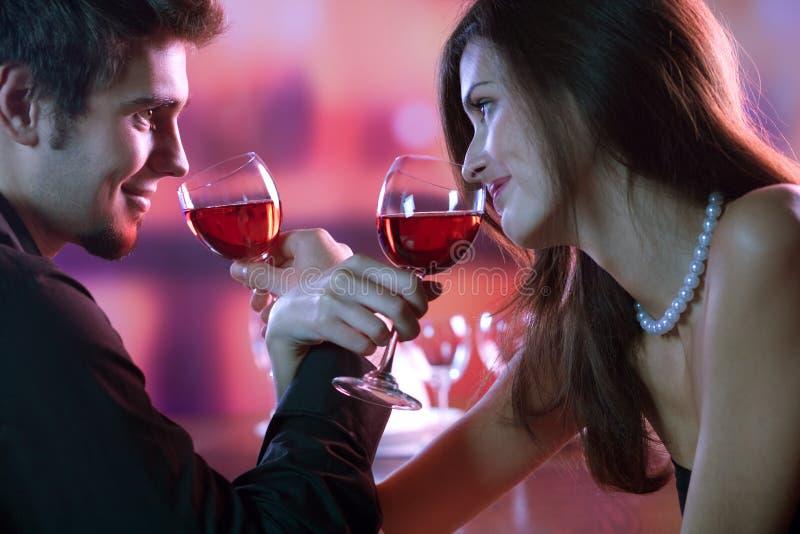 Jong paar dat een glas rode wijn in restaurant deelt, celebrat royalty-vrije stock foto