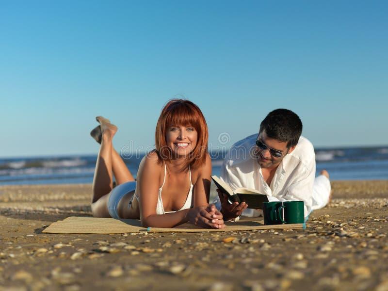 Jong paar dat een picknick op strand heeft royalty-vrije stock afbeelding