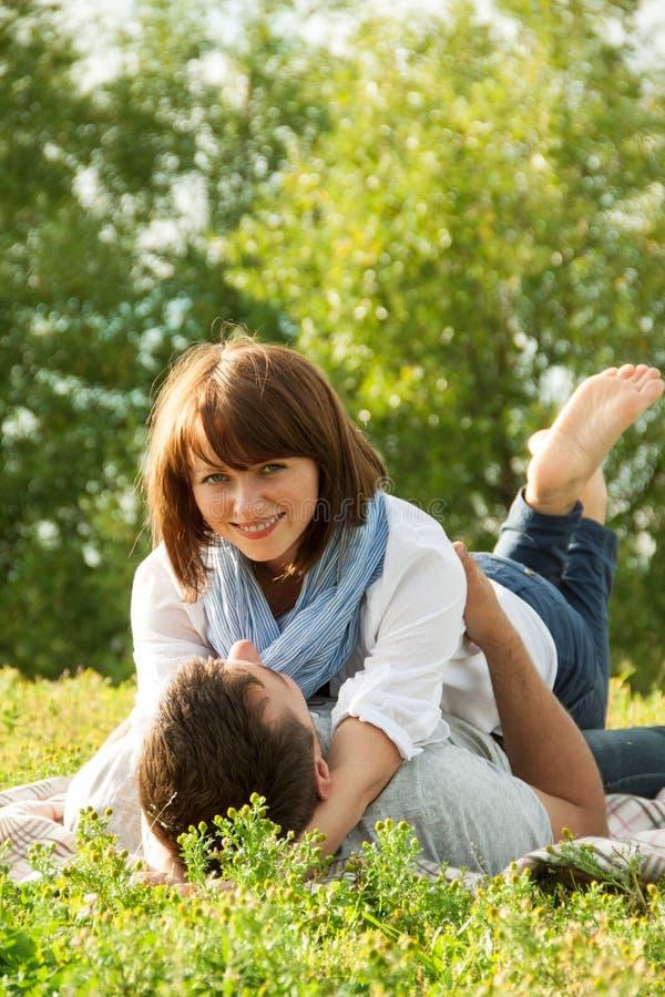 Jong paar dat in gras bepaalt en elkaar koestert royalty-vrije stock fotografie