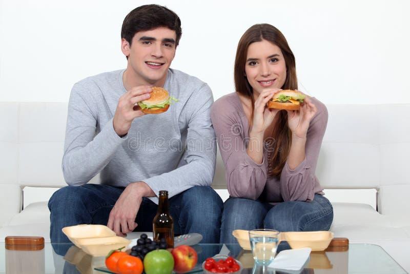 Jong paar dat hamburgers eet stock afbeeldingen