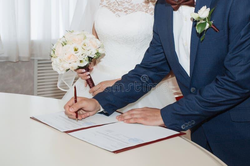 Jong paar dat huwelijksdocumenten ondertekent royalty-vrije stock afbeelding