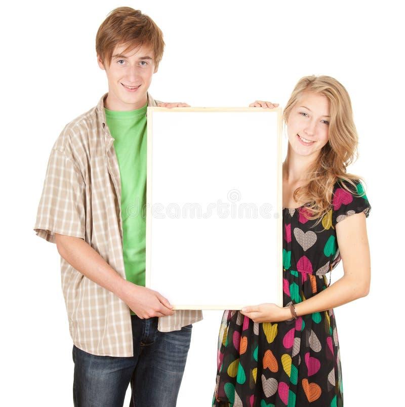Jong paar dat leeg aanplakbord houdt royalty-vrije stock afbeelding
