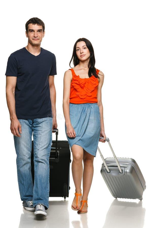 Jong paar dat met koffers loopt royalty-vrije stock foto