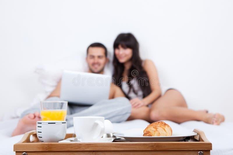 Jong paar dat omhoog in bed met laptop ligt stock foto