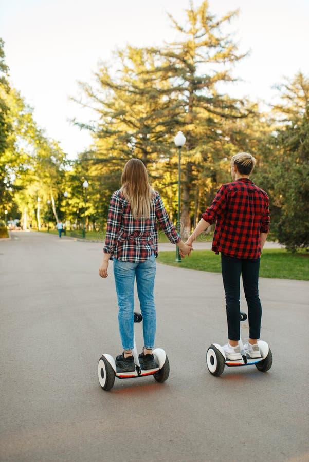 Jong paar dat op gyroboard in park berijdt, achtermening royalty-vrije stock fotografie