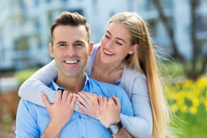 Jong paar dat in openlucht glimlacht stock foto's