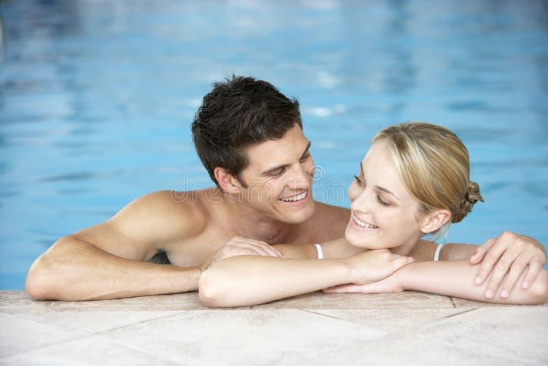 Jong Paar dat in Pool zwemt royalty-vrije stock afbeelding