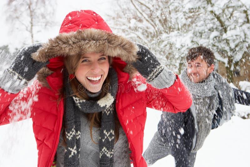 Jong paar dat sneeuwbalstrijd heeft stock foto