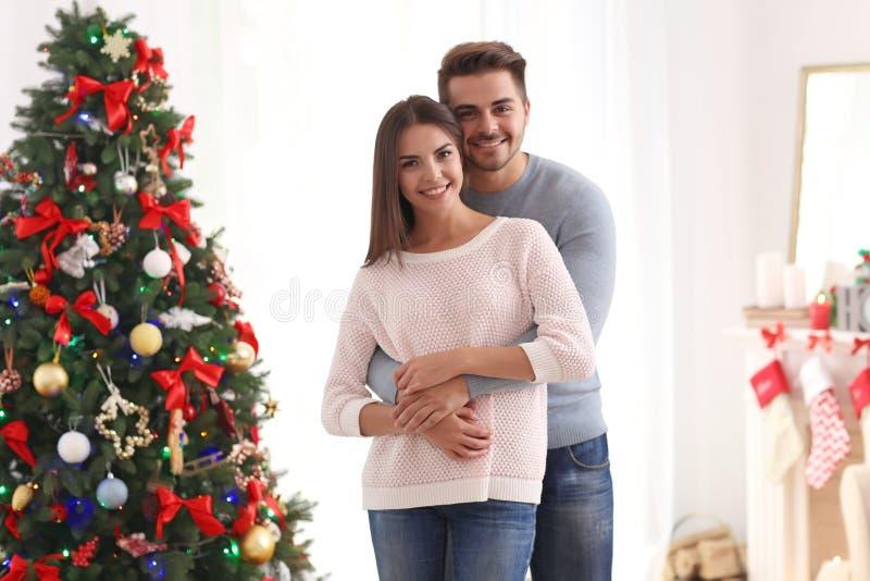 Jong paar dichtbij Kerstboom in ruimte stock afbeelding