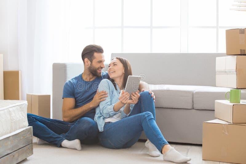Jong paar die aan een nieuwe flat zich samen verhuizing bewegen stock afbeelding