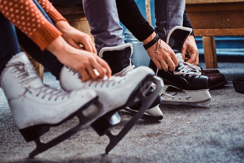Jong paar die aan het schaatsen voorbereidingen treffen De close-upfoto van hun handen die schoenveters van ijshockey binden scha royalty-vrije stock foto