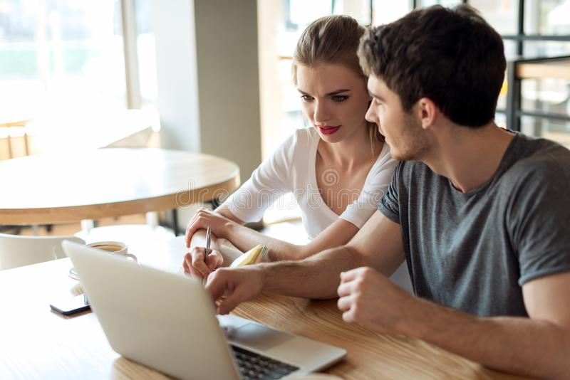 jong paar die aan laptop samenwerken terwijl het zitten bij lijst royalty-vrije stock afbeeldingen